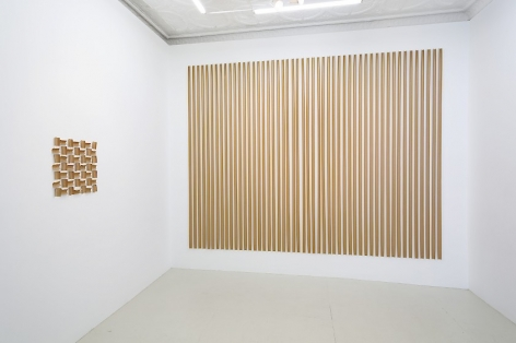 Installation view of 2 gummed paper tape installations by Thomas Kovachevich, one that takes up an entire wall and another that include 49 squares of paper tape installed in a square
