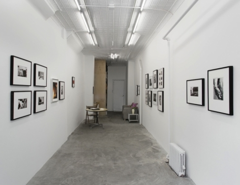 A view of the gallery from the front, with images installed salon-style throughout.