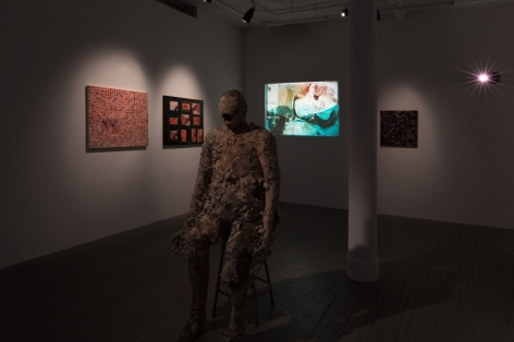 A photograph of the gallery with a bronze figural sculpture in the foreground; 3 flat works installed on the wall with spotlights, and a video on the back wall near the corner with a blue abstract image.