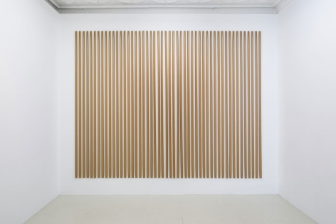 An installation of gummed paper tape, pinned at the top and bottom, in a rectangular arrangement of strips, taking up an entire wall