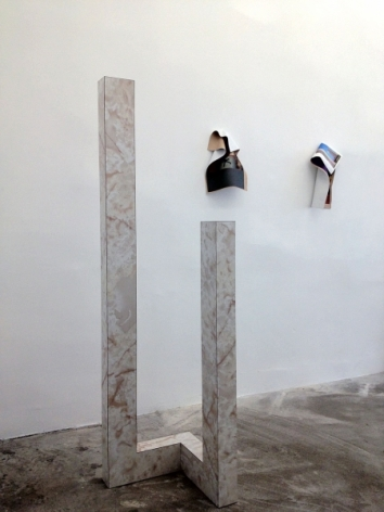 A photograph of one sculpture with 2 photographic works on the wall in the background