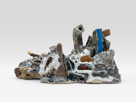 A ceramic sculpture with varied lusters and personal decals, as well as trompe-l'eoil items such as tubes, broken vessels, and other objects.