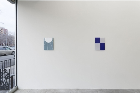 A photograph of 2 enamel paintings on a grey wall. The front window is visible at left.