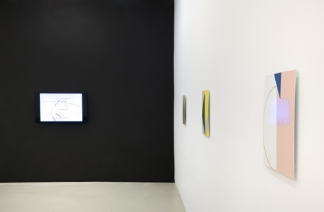 a black wall with a monitor hanging on it and three geometric abstract paintings in different colors viewed from the side