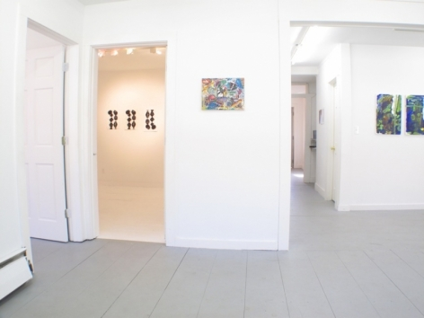 A photograph of the interior of the gallery: 3 image are in a separate room in the background, one is on a wall in the foreground, and at right we see 2 works partially