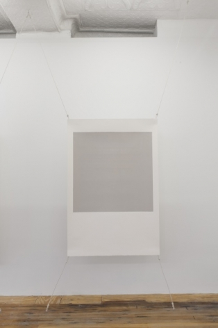 A photograph of one screenprint, stretched at all 4 corners. The center is grey and the framed around it is white. The work resembles a polaroid in it's arrangement.