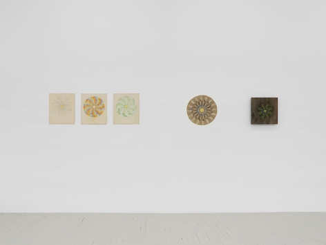 Left to right: an installation of three mandala drawings (colored pencil on paper), one mandala depicted on cardboard, and a mandala on a piece of wood.
