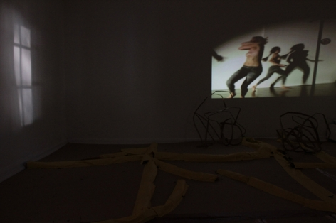 A photograph of a video projection, the room is otherwise dark. On the ground are barely visible sculptures.