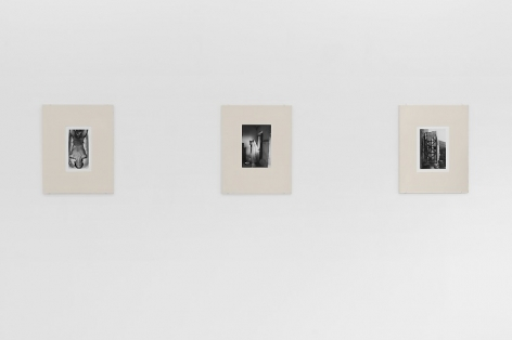 An installation view of 3 black and white Guibert photographs, placed in cream-colored frames made from watercolor paper, hung on the wall