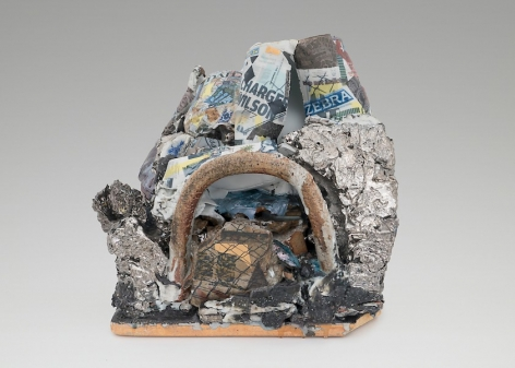 A mixed stoneware sculpture with a central arc made of stone. There textured surfaces surrounding it are painted with silver luster. Above those elements are varied jagged surfaces that host decals applied by the artist of newspaper articles and a chainlink fence print.