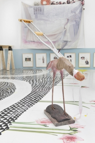 A photograph of a sculpture installed on the ground, made of a crutch attached to the body of a flamingo. In the background are a series of framed works hung low on the wall, contents illegible. There is also an artwork make of fabric above those framed works.