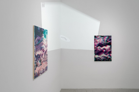 A detail of two artworks situated around the corner. Here we see a video projected onto the gallery wall and paintings. The video is a projection of the interior of the gallery itself.