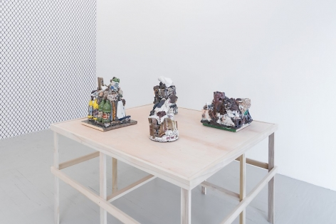 A photograph of a raw wood platform holding 4 ceramic sculptures. At left we see an excerpt of the gallery's temporary wall, upon which is mounted a chainlink fence wallpaper.