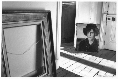 A black and white photograph of an interior of a home. At the left is an empty frame leaning against a wall. In the mid-ground is an androgynous portrait of a person in a hat in a coat. There is a long shadow cutting through a doorway to the left of the portrait, and a lock to a door to the right.