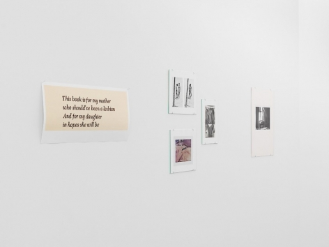 A photograph of the artworks on the temporary wall: there is a single work with text, 3 works hung in a loose triangle to the right, then a single photograph by Guibert of a man hunched over a desk with light streaming through a window above his head.