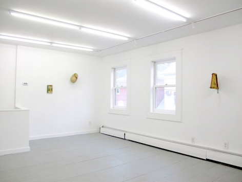 A photograph of 3 artworks hung on 2 walls, separated by 2 windows