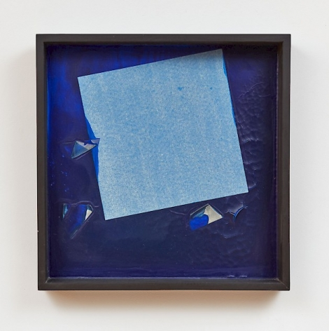 A composition with a base of thick blue paint. There is a square made of tissue paper near the center, tilted to the left. The square has taken on a slight blue hue, and there are several punctures in the bright blue that appear to be paper beneath it.