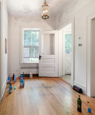 A photograph of the room with a view of the door and window, detergent and liquor bottles on the ground