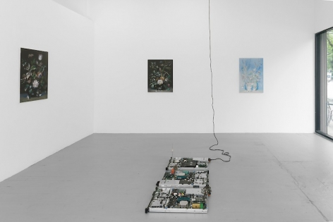 A photographs of 3 paintings of a still life of flowers with a circuit board sculpture on the ground.