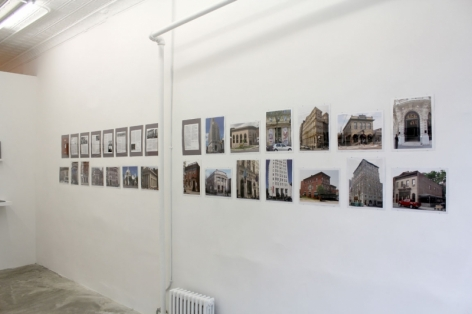 A photograph of color photographs of bank facades, in 2 rows on the wall unframed