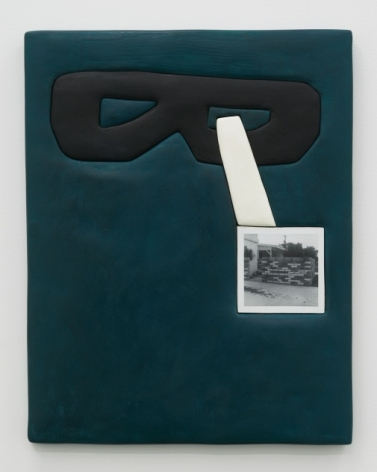 A dark teal background with a black eye mask on the top quarter of the surface. At right intersecting the mask and moving downward is a white quadrilateral. At the bottom of the shape approximately in the center-right of the canvas is a square photograph in black and white.