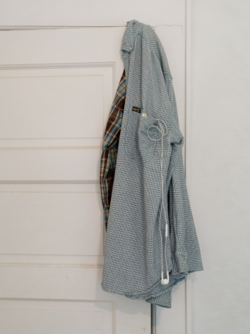 A close-up photograph of the shirt over the white door with headphones coming out of the pocket