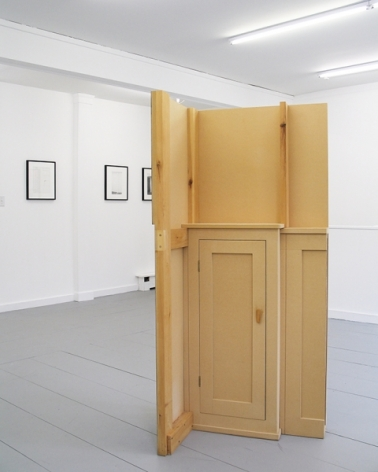 A photograph with the floor sculpture from the back which is natural wood tone. There are 3 works on a far wall in the background