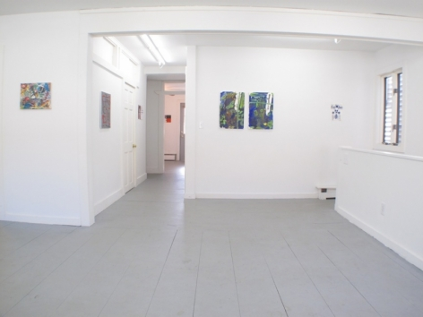 A photograph of the gallery with 2 works in the hallway, one work at left and 3 at right in the main room, and one work visible at the end of the hallway in the background