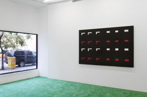 A photograph of the front of the gallery with the window at left and a black, red, and white artwork on the right wall.