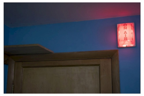 """A photograph of an illuminated """"ON AIR"""" sign that is lit in red. It is above the frame of a wooden door, which is cropped at the top hinge of the door. The wall is blue."""