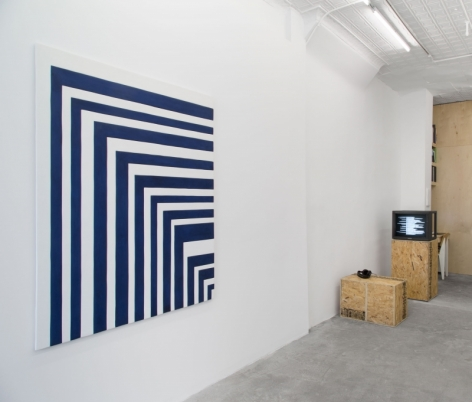 A photograph of a large artwork on a wall (blue and white lines) with a monitor in the background