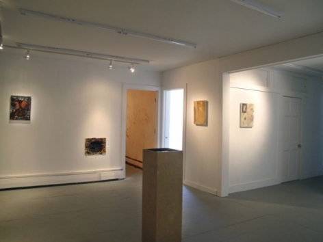 A photograph of 4 flat works on 3 walls. There is a pedestal in the middle of the room