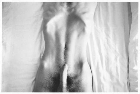 A black and white photograph of the naked torso of a man on white sheets. His erect penis juts from the bottom-center of the frame, and his ribs are pronounced at the top-center of the frame.