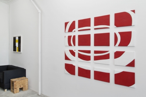A photograph of a large red and white work hung on the wall, and to the left a smaller framed work (black, yellow)