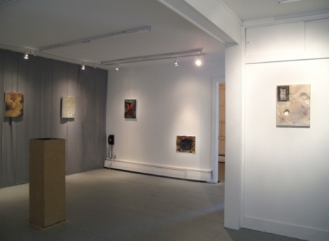 A photograph of the room: 2 works on a gray back wall with a wooden pedestal at left. There are 2 works on the far wall, and a work closer on the right wall