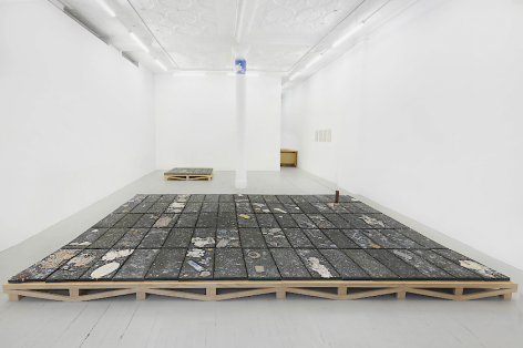 An installation image of the entire gallery, including 2 black clay tiled pieces installed on the floor (large in the foreground; smaller in the background) as well as a swatch of blue sky adhered to the top of a white concrete column in the center of the room