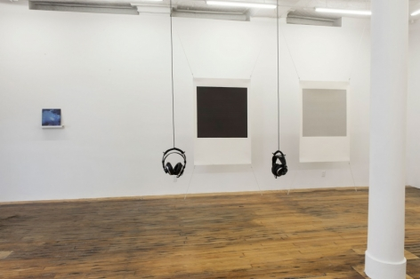 A photograph of the interior of the gallery. There are 2 sets of headphones, Tom Martin's piece at left on the wall in the background, and 2 screenprints by Bergvall stretched at the four corners on the same wall.