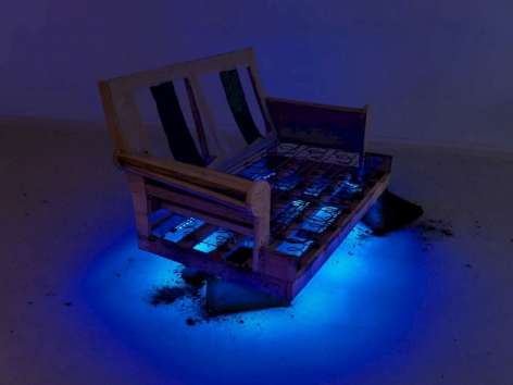 A photograph of an illuminated wooden couch, with blue LED lights underneath it. The couch is propped up on sandbags.