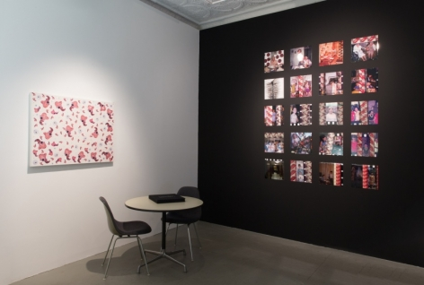 A photograph of the back office of the gallery. There is a small table with 2 chairs beneath a flat artwork installed on the wall. The opposite wall is painted black and hosts 20 stills from Price's films.