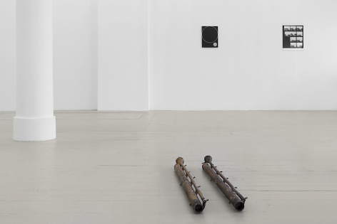 An installation view of K.R.M. Mooney's bronze sculpture installed on the floor, with an enamel painting by Ulrike Muller behind it and at left; a Zoe Leonard photograph at right, both black and white, hung on the wall.