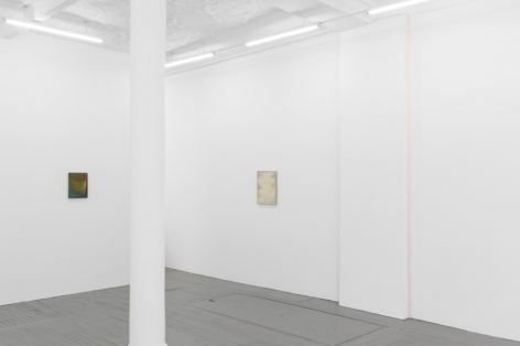 A photograph of the gallery that includes 2 Monick paintings in the background on 2 walls perpendicular to one another. On the right wall, there is also a pink ribbon artwork installed in the corner.