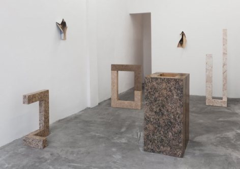 A photograph of the back of the gallery with 4 sculptures on the ground and 2 photographic works on the wall