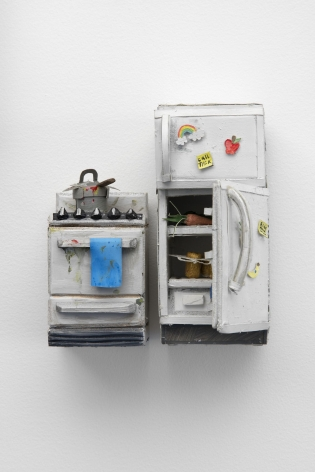 A stove with a dirty pot upon it and a refrigerator that is open, crafted from paper and foam. The two items are next to each other with a small space between them, hung on the wall. The open fridge has items within it (a carrot, a brown object) and magnets on the exterior.