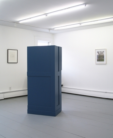 A photograph of a sculpture in the center of the gallery with 2 works on 2 walls, perpendicular