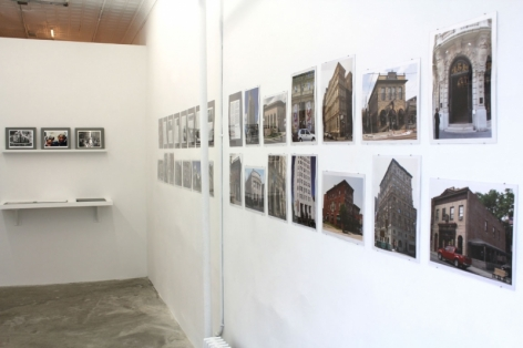 A photograph of the gallery walls with bank facades on the left and 2 shelves on the back wall, barely visible