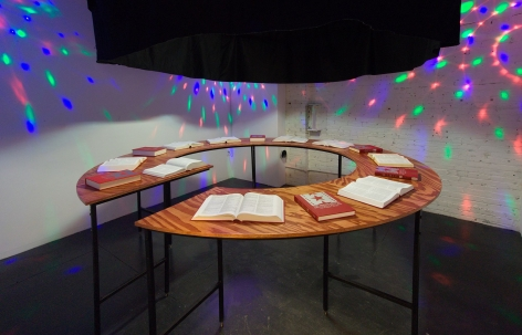 An installation of 15 books on a circular wooden table, some open and some closed. There are red, green, and red LED lights on the walls.