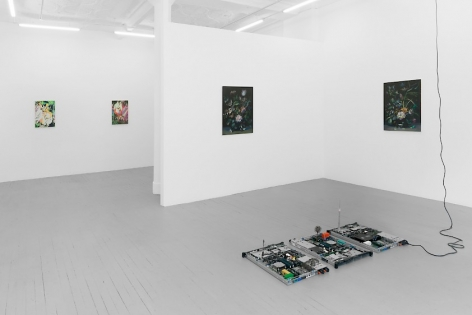 A photograph of 4 paintings on 3 walls, and a sculpture of circuit boards on the ground.