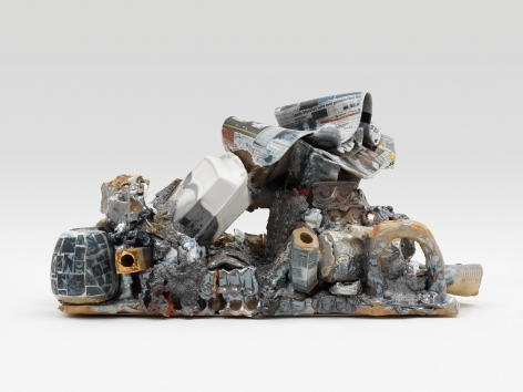 A ceramic sculpture that includes trompe-l'eoil elements such as styrofoam clam shells, a newspaper, and numerous decals created by the artist.