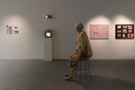 A photograph of the interior of the gallery with a side profile of the bronze sculpture in the foreground. On the wall behind the sculpture are 2 wall works at the right. To the left is a small monitor on a pedestal with an illegible video upon it. To the left of that on the wall are 3 small illegible works (appear to be in black and white)