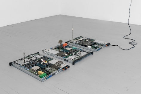 A photograph of 3 circuit board sculptures installed on the ground.